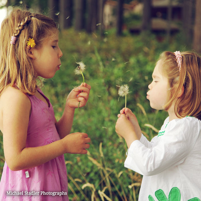 Two little girls blowing dandelion seeds